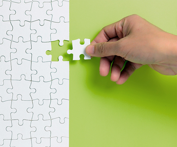 hand putting the last piece of white puzzle for business
