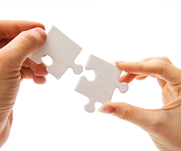 white-puzzle-fitting-together-with-hands
